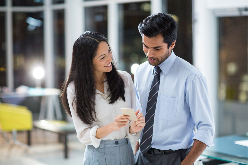Businesswoman showing mobile phone to colleague in the office-1