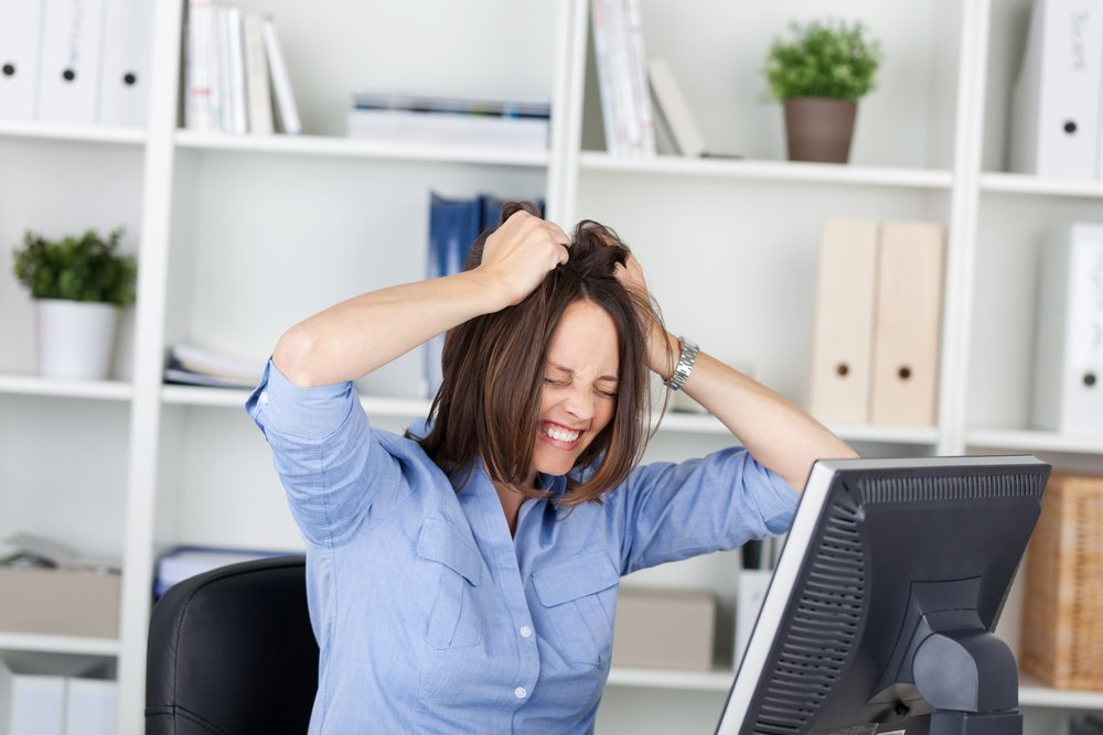 Irritated businesswoman pulling her hair while sitting in office