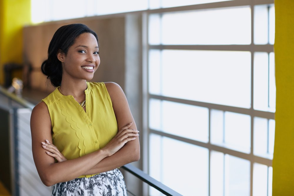 Confident businesswoman smiling in bright modern office