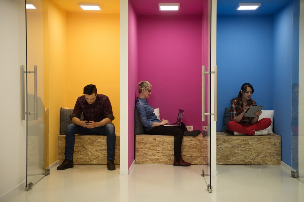 Three individuals working on their devices in separate colorful spaces